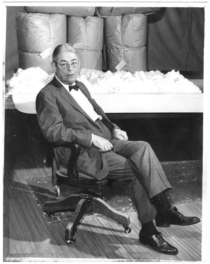 Mr. Lamar Fleming seated in the cotton sample room